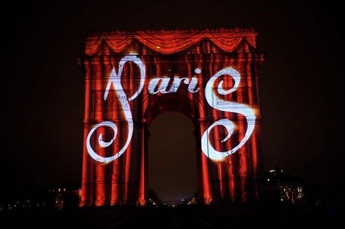 """2016年12月31日夜,在法国巴黎,""""巴黎""""字样的图案被映在该市标志性建筑凯旋门上。"""